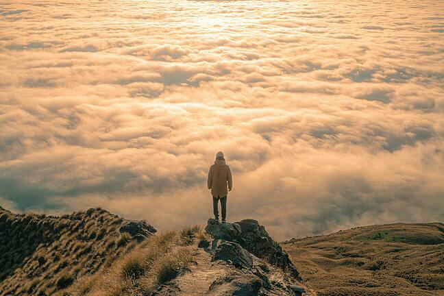 A person stands on the top of a mountain, with the clouds below them. They are clearly staring into the distance.