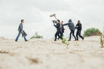 A film crew shooting a man walking along sand dunes