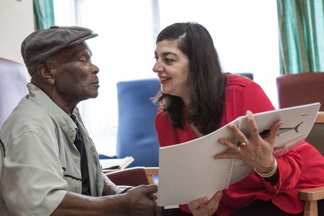 Photograph of two people talking with each other in a care home, whilst one of them holds a bound booklet