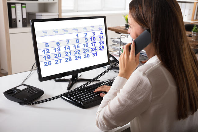 A woman on a telephone looking at a computer screen with a calendar on it.