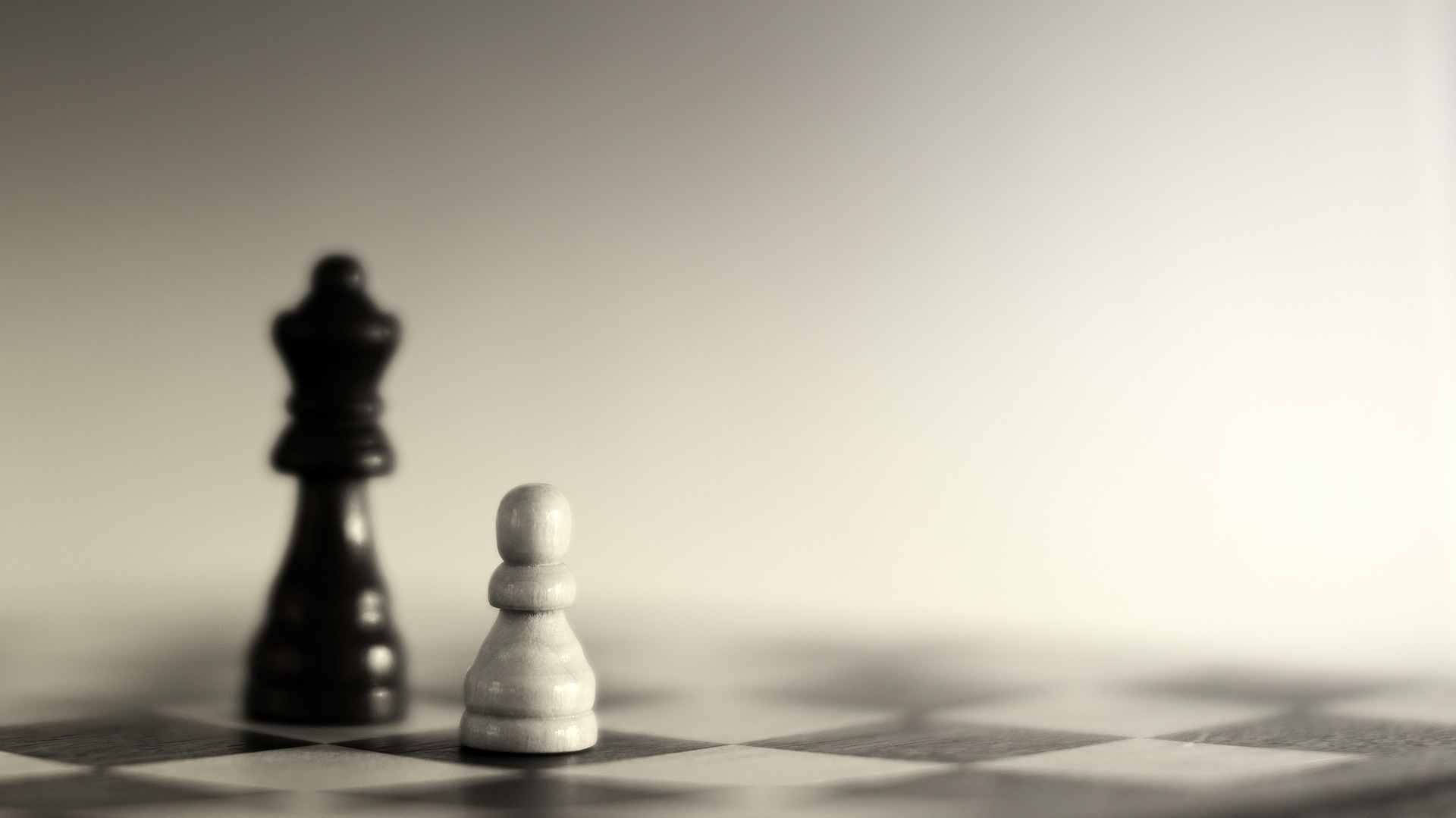A chess board with 2 chess pieces - a black bishop and a white pawn