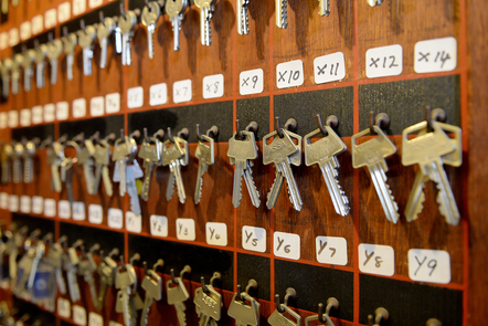 A row of room keys hanging on a wooden board.