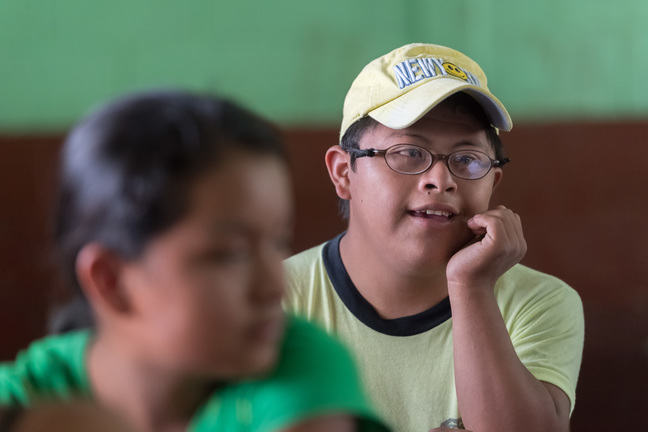 A teenage boy with Down syndrome sitting in a school classroom. He is wearing a baseball hat and glasses and leaning on one hand.