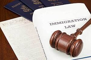 Image of passports, documents and book on immigration law with a gavel on top