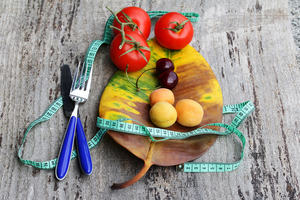 A photograph of cherries, apricots, tomatoes, tape measure and cutlery neatly placed on a large leaf.