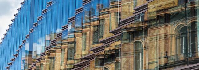 Old building facade reflection in modern building glass facade.