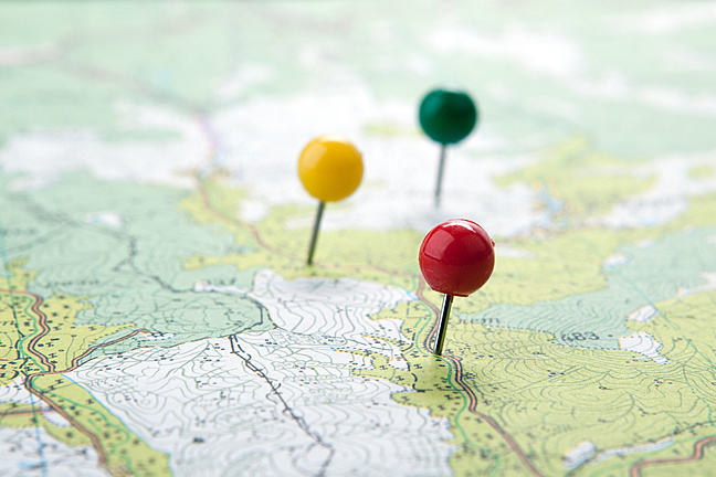 Three markers on a geographic map with round head of different colours (yellow, green and red)