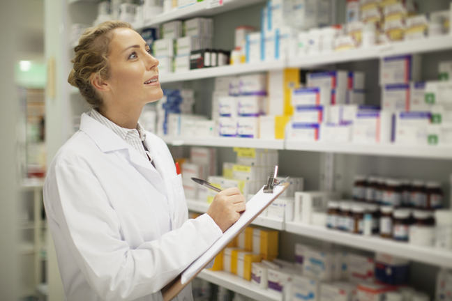 A female pharmacist checking stock in a medicine storage facility.