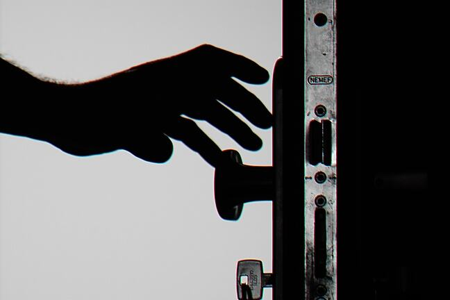 Silhouette of a door in black and white, with a hand reaching out to grasp the handle.