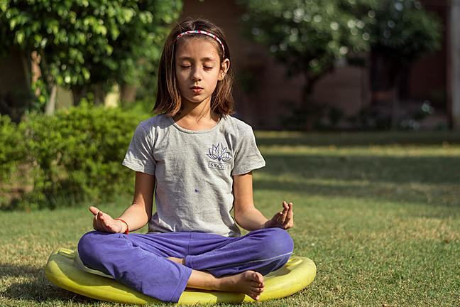 A young girl practicing meditation