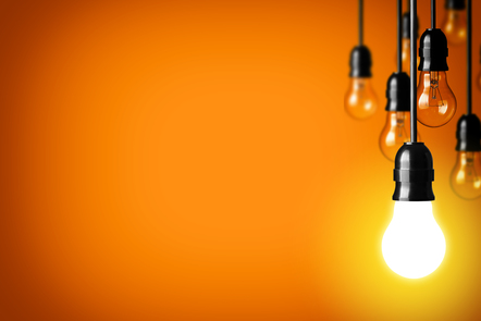 Six lightbulbs hang from black wires against an orange background. The clostest one is lit with a bright yellow-white light