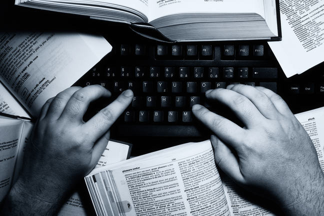 A person typing on a computer surrounded by books.