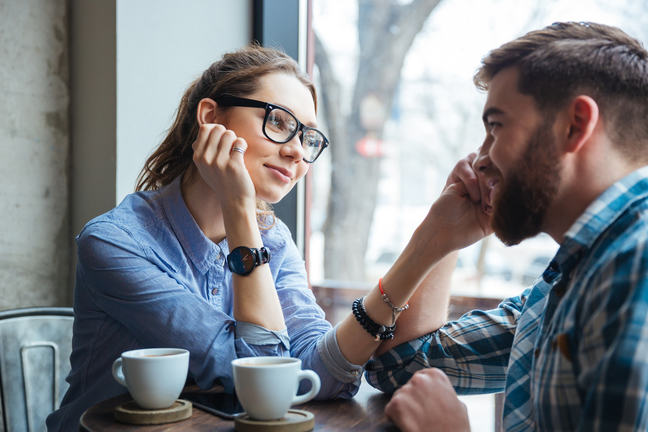 A woman with glasses looking at her partner in a coffee shop.