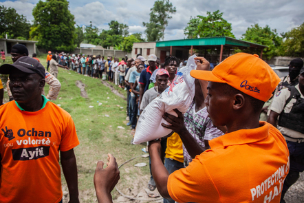 Haitians stand in line to receive a bag of food as part of the humanitarian aid.