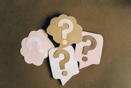 four grouped question marks in white, beige and brown shades cut out of paper on a brown paper background