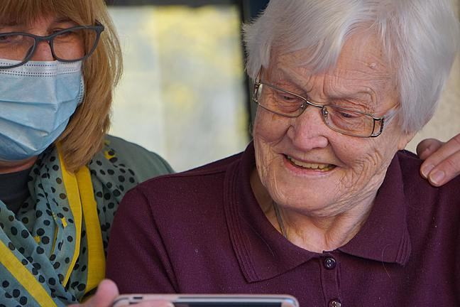 A female carer wearing a face mask is next to an elderly woman, showing her information on a screen
