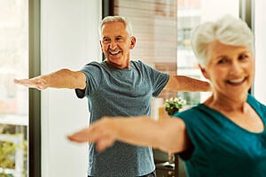 A man and women in their sixties doing exercises at home