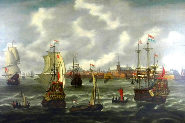 The painting in strong colours shows Dutch cogs, two anchored ones and two with set sails, in the foreground smaller ships and boats. In the left background more ships as well as a city view in the central background.