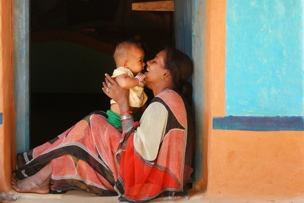 A mother in Bangladesh sits in a doorway holding her baby, and laughing.