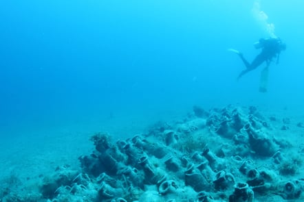 A diver exploring some amphora from a shipwreck