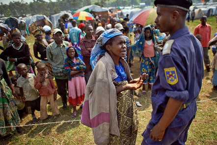 A women speaks with a policeman during a food distribution in camp Butembo for displaced persons on January 14, 2013 in Goma, Democratic Republic of Congo.