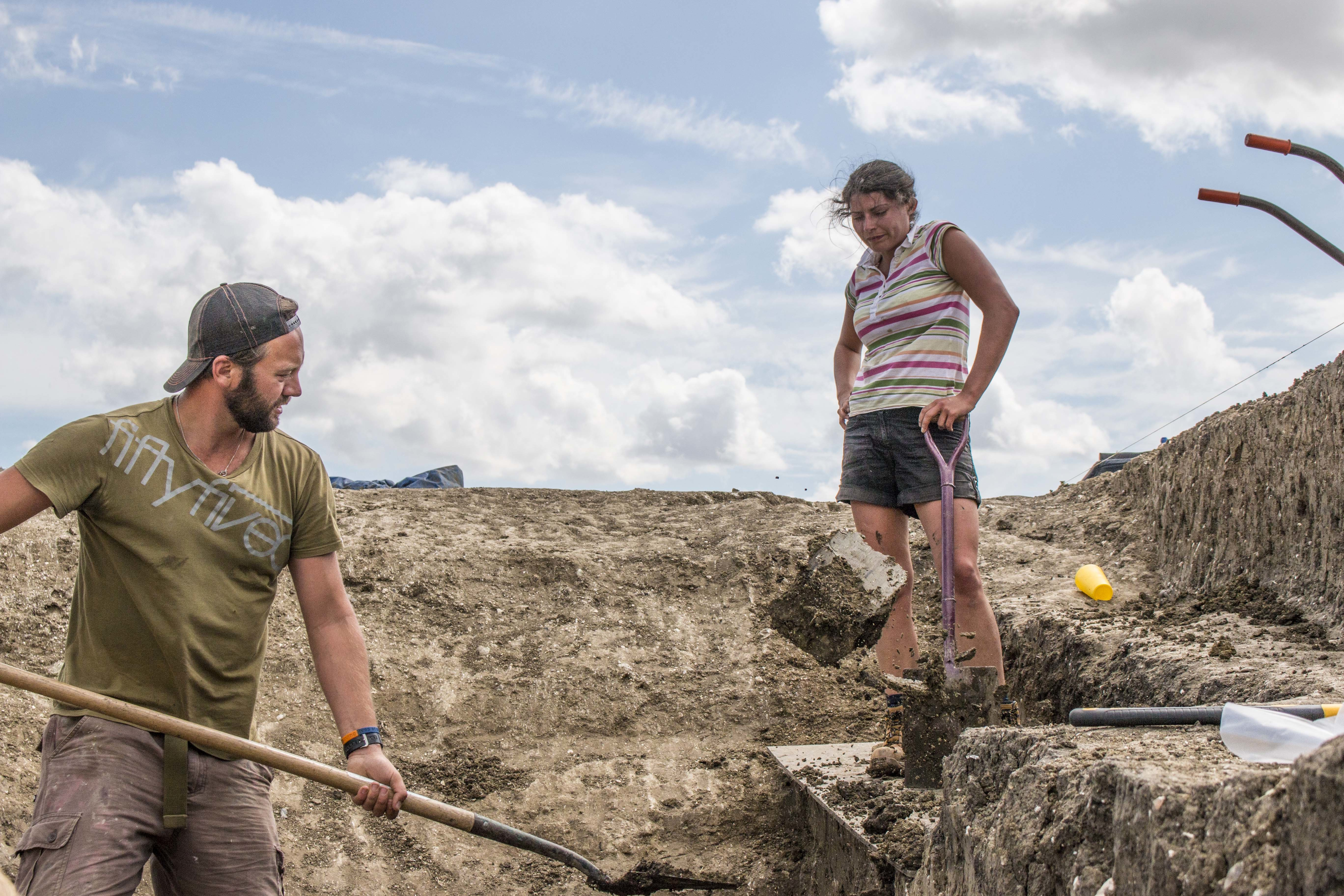 Two people shovelling in a trench, at an excavation site