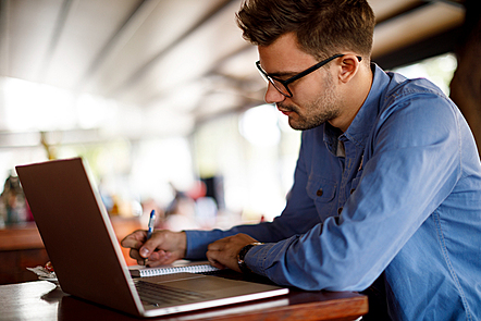 Young man at a desk with a laptop and writing notes on a pad.