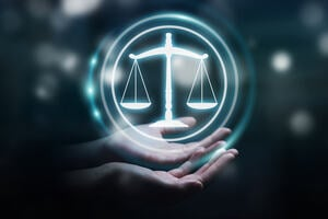 a picture of open hands cradling a graphic of the glowing scales of justice
