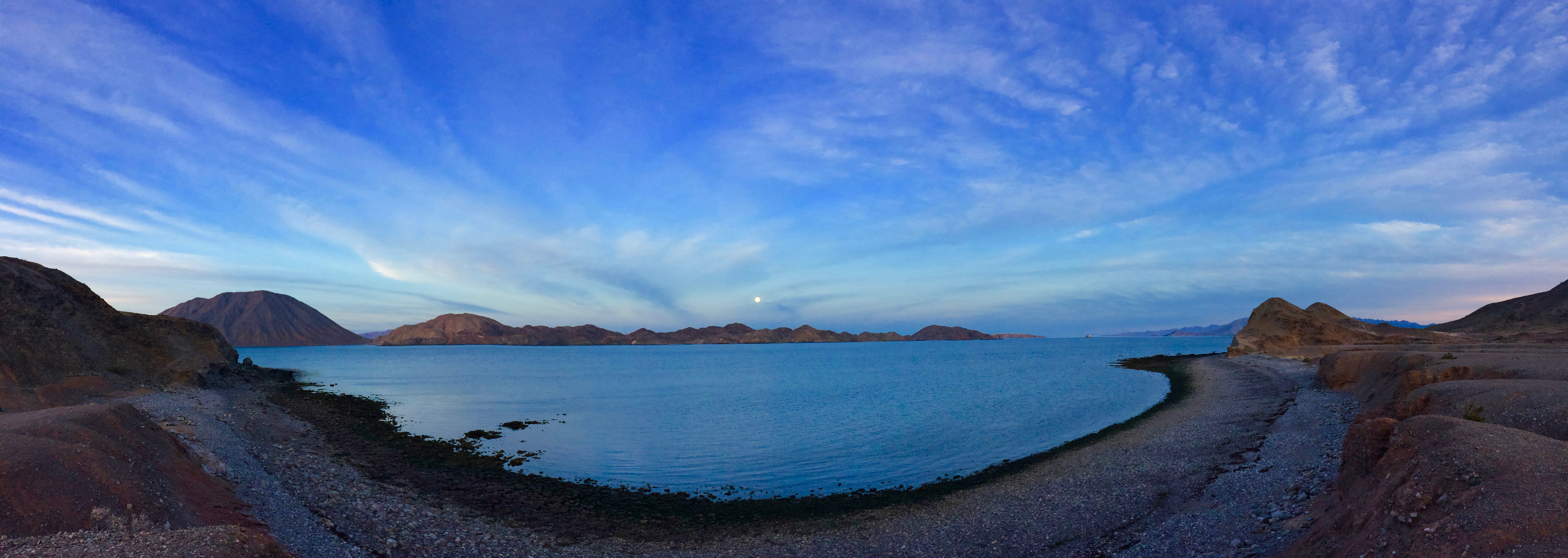 A panoramic view of moonrise over a bay.