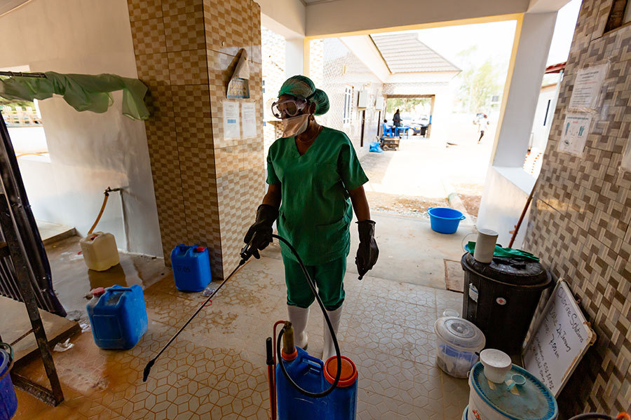 A nurse wearing a scrub suit, gloves, mask, goggles and hairnet is holding decontamination equipment which has a long tube with a nozzle and a blue container. She is spraying the floor of the building. There are containers at her side.