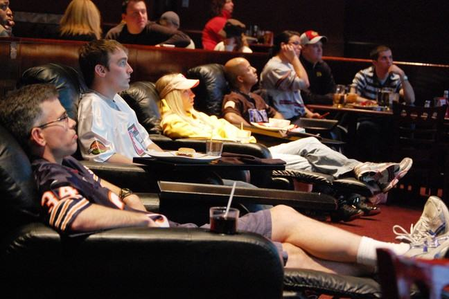 People sitting in La-Z-Boy recliner chairs with fast food and soft drinks