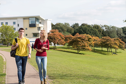 Two students walking across campus