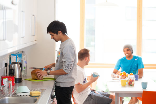 A photo of a shared kitchen with one person standing and slicing a loaf of bread and 2 people sitting at the kitchen table talking.