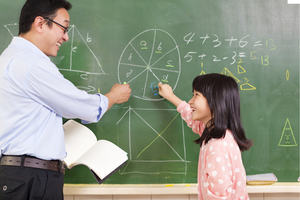A teacher and child at a blackboard