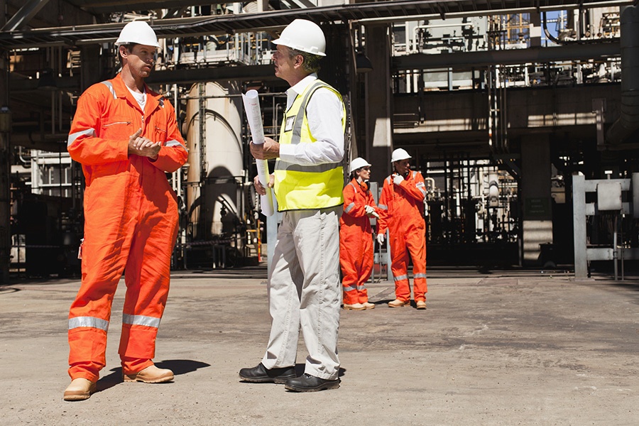 Two men in high-vis protective clothing standing near a building site.