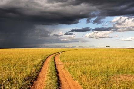 Dirt track with grey cloudy sky overhead in the Masai Mara