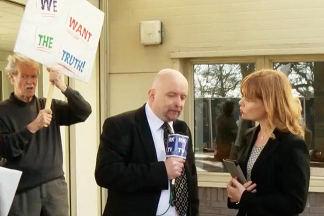 Entrevistador de televisión haciendo preguntas a un representante del hospital con un manifestante en el fondo.