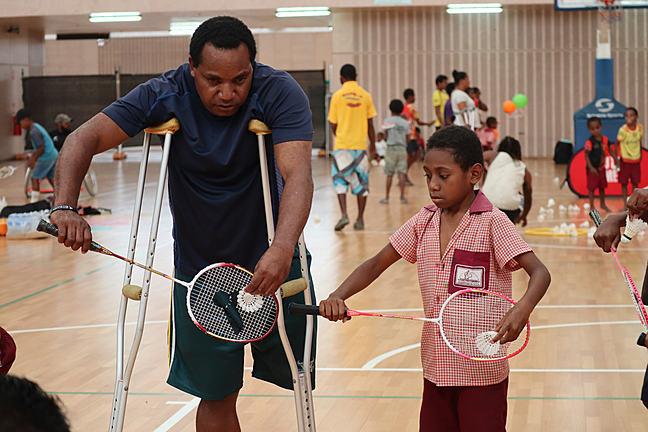 Para athlete teaches young boy how to play badminton Papua New Guinea