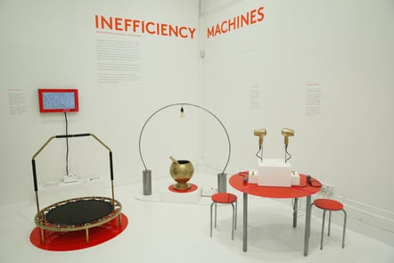 Decorative image, an art installation with the words Inefficiency Machines on the wall. There are 3 machines which demonstrate how power is generated but in awkward fashions. Meret Vollenweider & Wasabii Ng,  Information Experience Design. 2016
