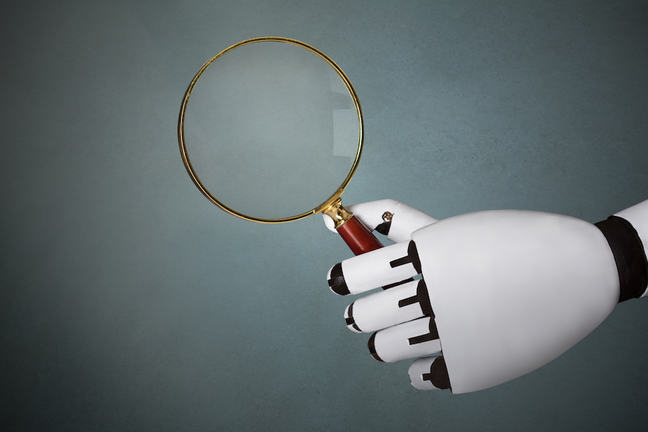 Robot hand holding magnifying glass