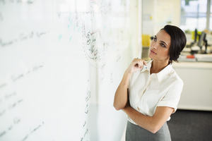 Woman looking at whiteboard diagram