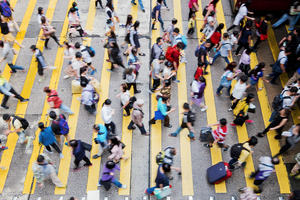 Many people crossing a road in a busy city