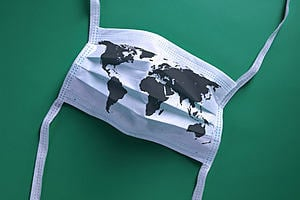 a white mask with an outline of the world across it on a green background