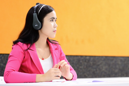 A student wearing headphones during the IELTS listening test