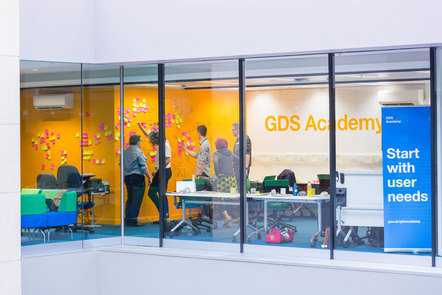 image of classroom with learners standing and looking at post its. On the wall it says GDS Academy and a sign says Start with user needs.