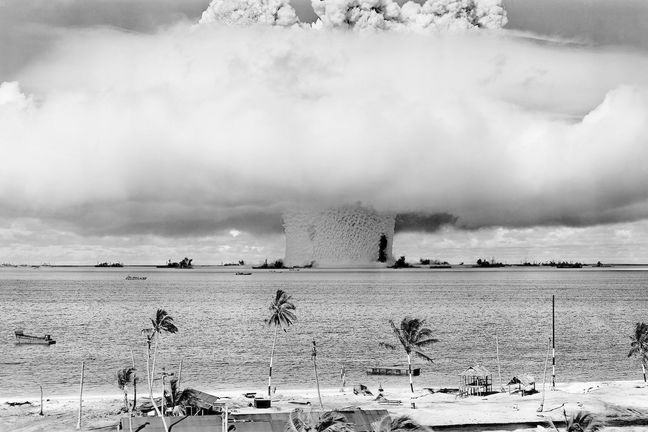 Photo Atomic Black and white photo image of atomic bomb Baker Detonation Wide Field view from Bikini Atoll Beach, 1946, with large white cloud in centre and palm trees on beach in foreground