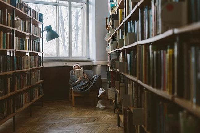 A photograph of a woman reading a book on a chair in a library