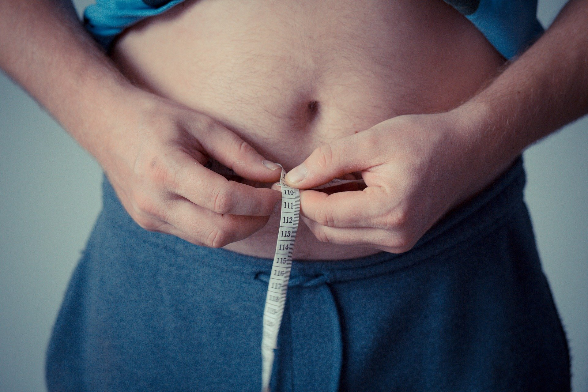 Overweight man holding measuring tape around belly