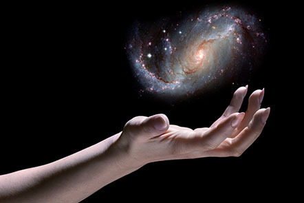 A hand reaching out, with a mini spiral galaxy hovering above it, over a black background.