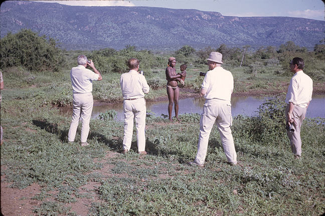 Four white men taking pictures of an African tribeswoman holding an infant by a pond in an open savanna.